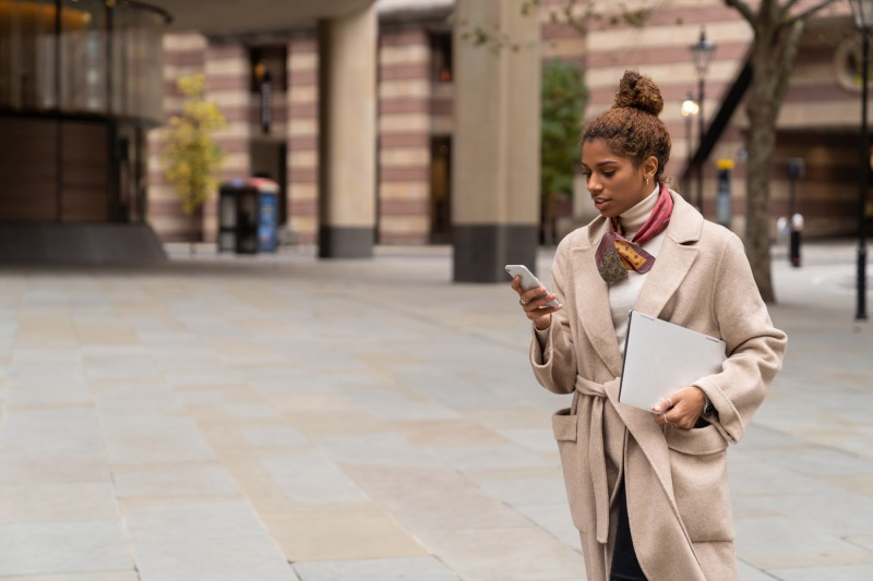 Young black woman looking at her phone and walking to work