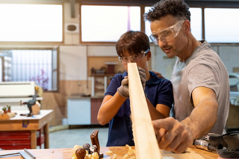 Father teaching son how to work with wood in a carpentry. Selective focus