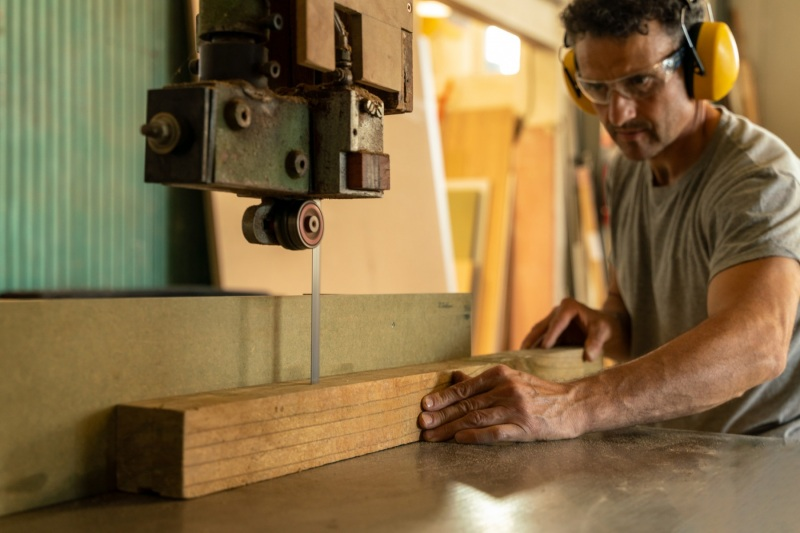 Carpenter cutting wood with a machine wearing earplugs. Selective focus