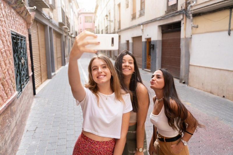 Group of young girlfriends taking a selfie while visiting a city