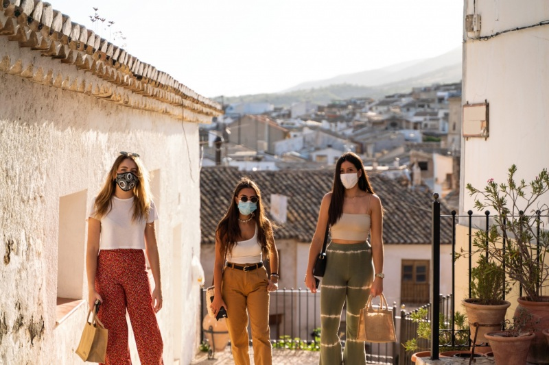 Group of girlfriends visiting a city and getting around wearing their face masks because of Coronavirus or Covid19