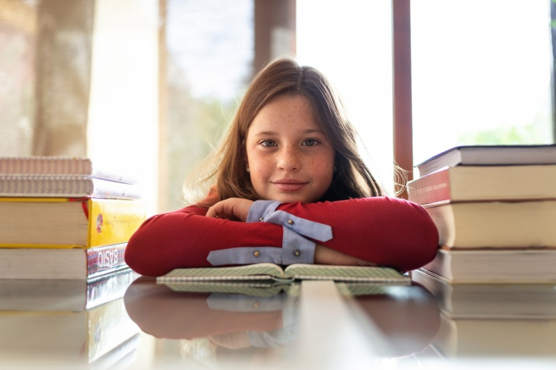 Young girl looking at the camera with arms on a book and s