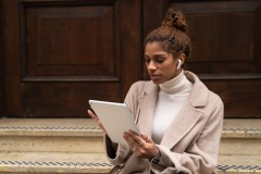 Young black woman working with an iPad and sat on stairs