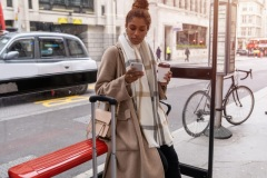 Young black woman traveling and waiting for the bus looking at her phone