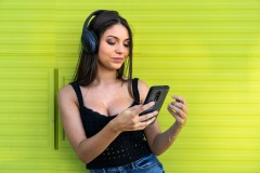 Young girl looking at her phone wearing headphones in a green background